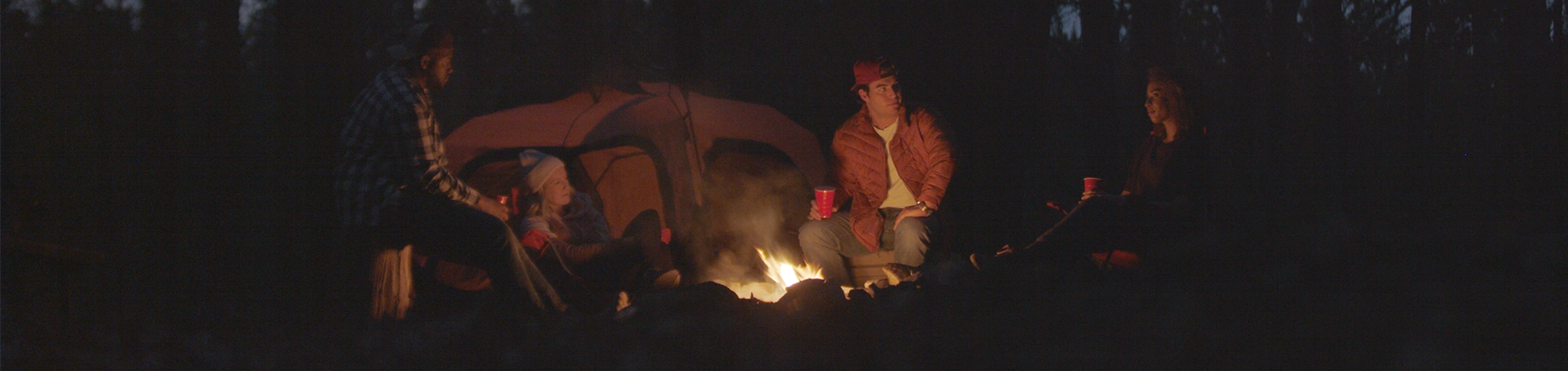 Friends sitting around a campfire together